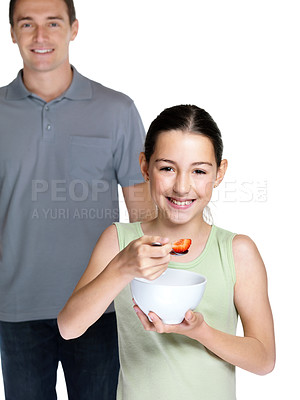 Buy stock photo Portrait of a happy small girl eating fruit salad while her father standing in background on white background