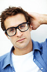 Thoughtful young man in glasses against white