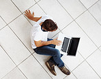 Relaxed young man sitting on floor and using laptop