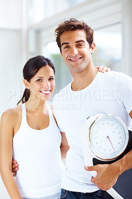 Buy stock photo Portrait of beautiful young fit couple standing together with a weight scale