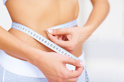 Buy stock photo Cropped image of a fit young woman measuring her waistline