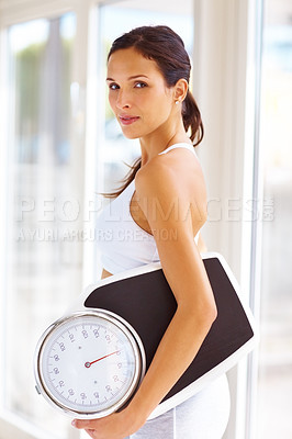 Buy stock photo Portrait of an attractive young woman holding weight scale