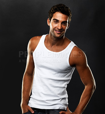 Buy stock photo Portrait of young man standing on black background and smiling