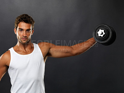 Buy stock photo Portrait of young man lifting dumbbell sideways on black background