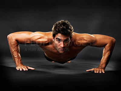 Buy stock photo Portrait of a muscular guy doing pushups on a black background