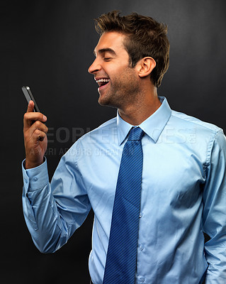 Buy stock photo Young business man reading a text message on his mobile phone and laughing on black background