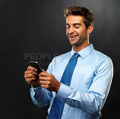 Buy stock photo Business man reading a text message and smiling on black background