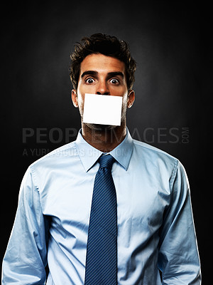Buy stock photo Portrait of shocked business man with paper covering his mouth on black background