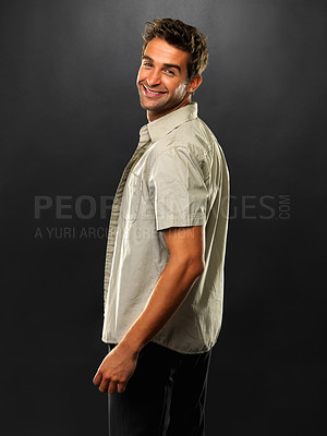 Buy stock photo Portrait of man looking over his shoulder and smiling on black background