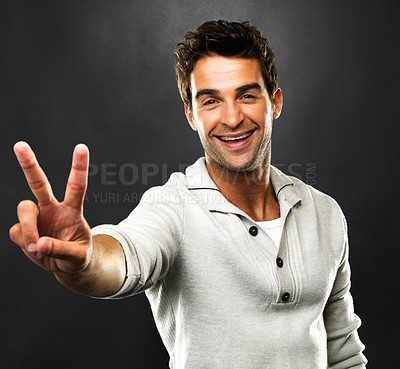 Buy stock photo Portrait of handsome smiling man holding up two fingers in a peace sign, isolated against dark background