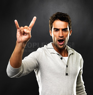 Buy stock photo Portrait of young man with rock sign on black background