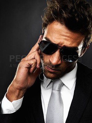 Buy stock photo Closeup of secret agent listening to instructions being conveyed to him through earphones on black background