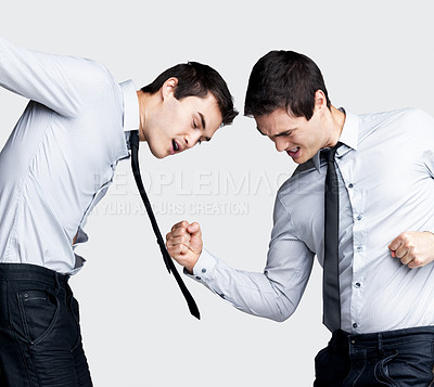 Buy stock photo Portrait of a psycho young business man fighting with himself against grey background