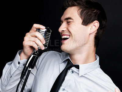 Buy stock photo Portrait of a successful young male jazz singer singing with his vintage microphone