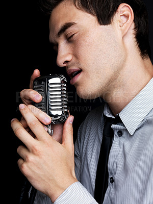 Buy stock photo Portrait of a young male star singer singing with old fashioned microphone against black background