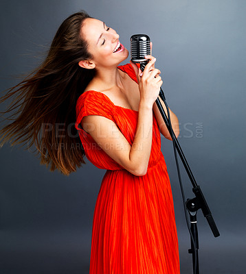 Buy stock photo Portrait of a happy young female jazz singer singing with old fashioned microphone