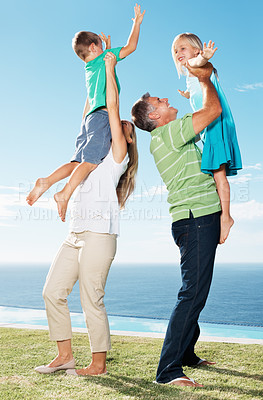 Buy stock photo Playful parents lifting their children up at park