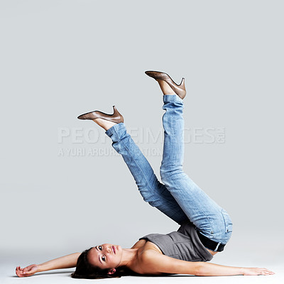 Buy stock photo Portrait of a crazy young woman lying in upside down posture against grey background