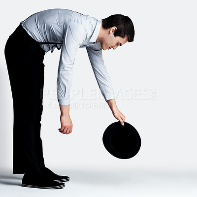 Buy stock photo Portrait of a handsome young man holding hat while bending against grey background