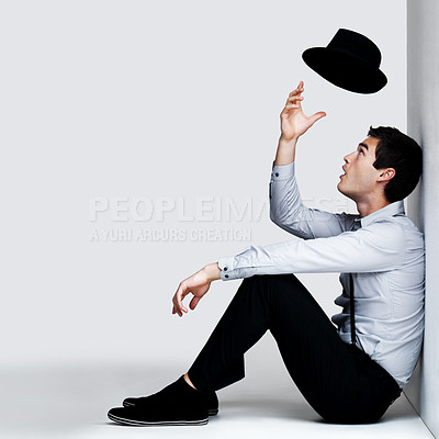 Buy stock photo Portrait of a stylish young man playing with his hat while sitting on the floor, isolated on white - copyspace