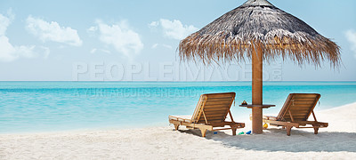 Buy stock photo Beautiful landscape with clear blue ocean, white sand, wooden reclining chairs and a palm-frond shade canopy