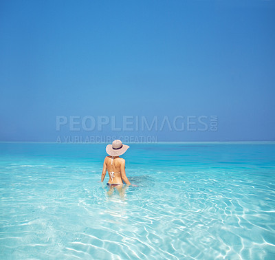 Buy stock photo Rearview of a woman standing waist deep in crystal clear seawater with bright blue sky - copyspace