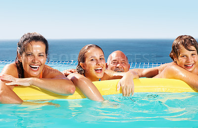 Buy stock photo Happy family of four floating on an inflatable tube in the water during a vacation - copyspace