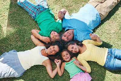 Buy stock photo Happy family with their heads together on the ground