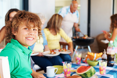 Buy stock photo Closeup of happy little boy with his family having meal together