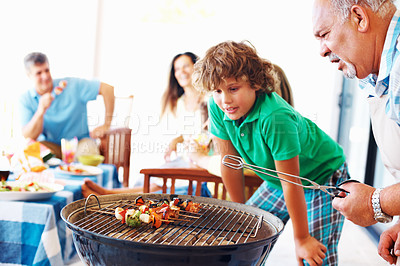 Buy stock photo Old man and grandson barbecuing vegetables with family in the background