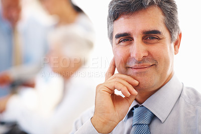 Buy stock photo Closeup of smiling business man with colleagues discussing in background