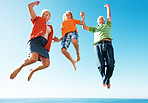 Excited old couple jumping in air with little boy