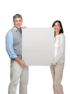 Buy stock photo Portrait of a happy mature man and woman holding an empty billboard on white background