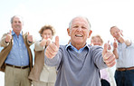 Joyful senior man showing thumbs up sin with his friends at back