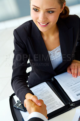 Buy stock photo Shot of a two businesspeople sitting a table shaking hands together over paperwork