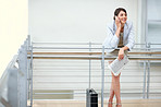 Successful business woman using cellphone by a railing
