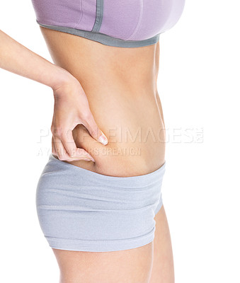 Buy stock photo Midsection view of a woman pinching skin for fat test on white background
