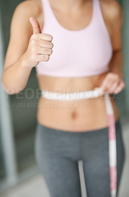 Female with a measuring tape around waist and thumbs up