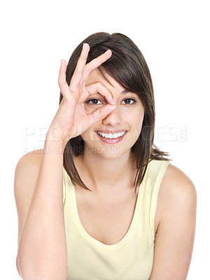 Buy stock photo Smiling cute Caucasian female looking through circled finger isolated against white
