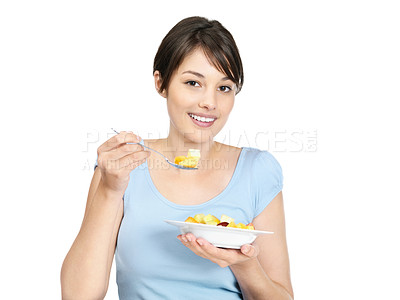 Buy stock photo Portrait of a smiling pretty female eating a bowl of cut fruits against white