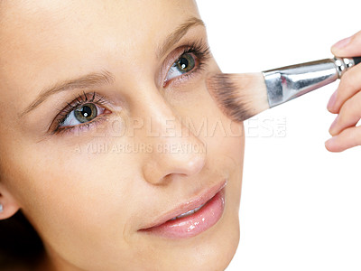Buy stock photo Closeup portrait of a cute young woman applying makeup on her face
