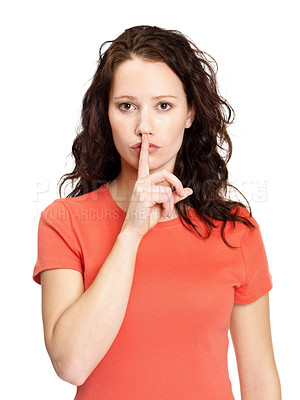 Buy stock photo Portrait of a pretty young woman gesturing silence with finger over her mouth