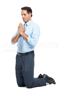 Buy stock photo Studio shot of mature businessman praying on his knees against a white background