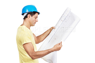 Buy stock photo Shot of a male architect looking at blueprints against a white background