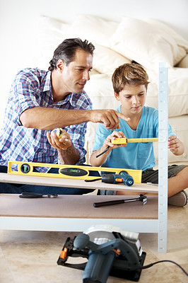 Buy stock photo Portrait of a small boy and his father measuring a wooden plank with tape measure in workshop