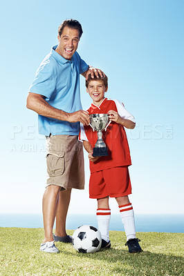 Buy stock photo Excited father and his son with a winners trophy of football standing together on field