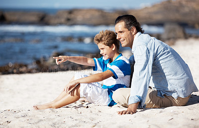 Buy stock photo Cute little boy pointing at the sea while sitting on the beach with his father - Copyspace