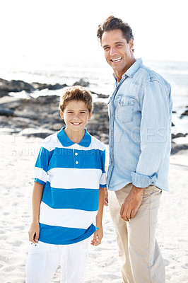 Buy stock photo Smiling young man with his small boy at the beach - Summer vacation