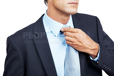 Buy stock photo Cropped shot of a businessman in a suit adjusting his necktie against white background