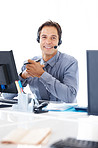 Confident business executive with headset working at his desk